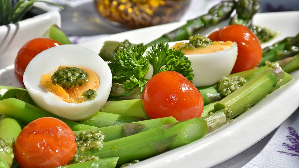 White platter with two garnished egg halves on a bed of celery, cherry tomatoes, and asparagus.