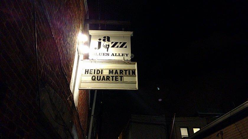 "A brick exterior is to the left, and a night sky is to the right. In the bottom right-hand corner, there are windows and a roof. In the center are two signs. The one on top reads ""Jazz Blues Alley"" with a finger pointing downwards. The lower sign reads ""Heidi Martin Quartet"". The signs are white, the writing is in black. Two floodlights light up the sign from the left."