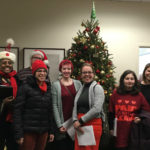 "Ten Christmas Carolers in an office posing smiled in front of a Christmas Tree. All are wearing festive attire, a few are wearing t-shirts that say ""DC Paid Family Leave""."