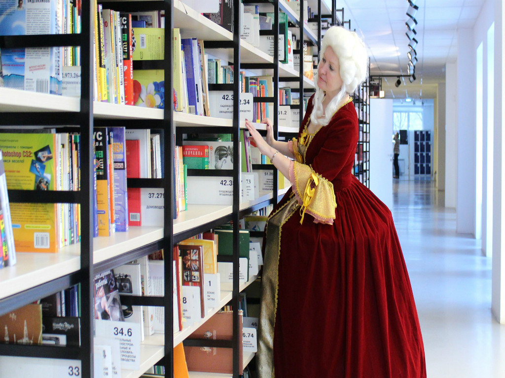 Beige bookshelves in a library on the left, which are mostly full with colorful books. A woman dressed as a queen in a white wig, red gown, and yellow garment looks toward the shelves with her left hand on the third shelf.