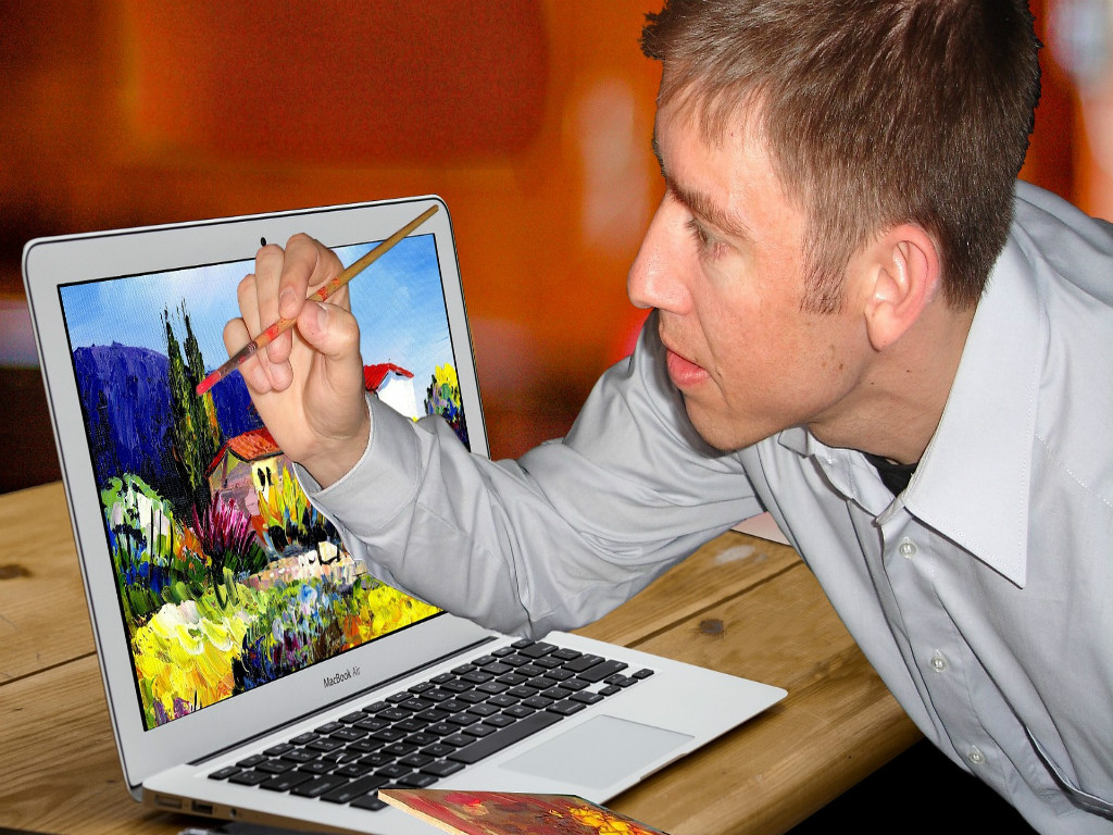 Man with blonde hair wearing a light blue collared shirt is facing leftward. He is painting something on his laptop with his right hand. The silver laptop is on the left side of the photo. The painting covers the area of the screen, and it is of a red-roofed, white-walled singe-story house surrounded by yellow, pink, and green plants, tall green trees, and mountains with a blue sky in the background.