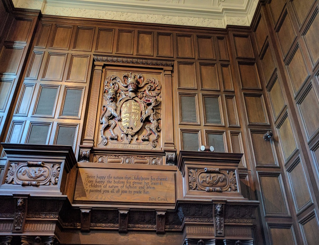 """In the lobby of the Folger Shakespeare Library. The upper part of a wooden wall over a doorway. There is a large crest and engraved underneath a David Garrick quote: """"Thrice happy the nation that Shakespeare has charm'd. More happy the bosoms his genius has warm'd: Ye children of nature, of fashion and whim. He painted you all. All join to praise him."""""""