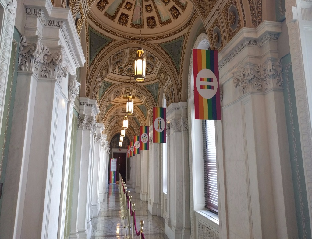 The view down a hallway in the Jefferson Building of the Library of Congress. Marble floor, marble walls and pillars, and a series of dome ceilings. There are windows along the right side, each with a rainbow flag and different LGBTQ-related symbols. A velvet rope divides the hallway lengthwise.