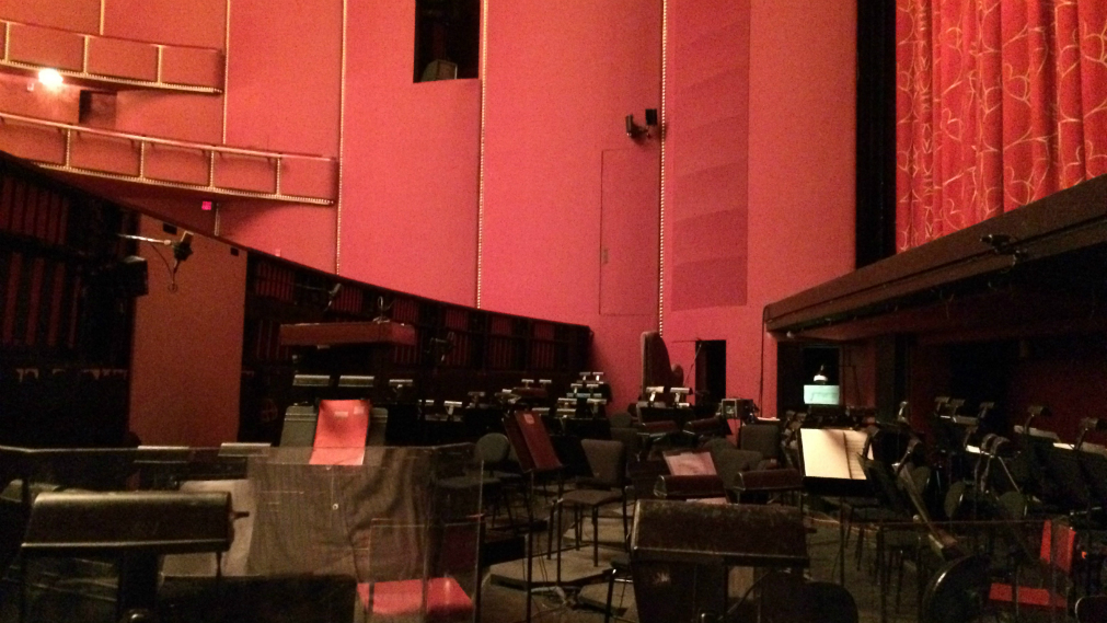 View from stage left of the Kennedy Center Opera House orchestra pit. To the left is the audience, to the right is the red and gold silk curtain. Down the middle, there are music stands and stand lights leading to a red wall.