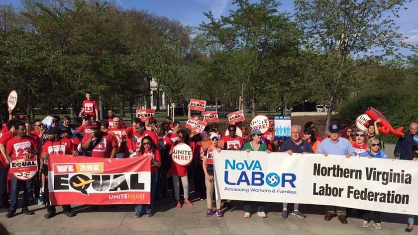 "People from a labor march, mostly in red t-shirts, stand with the DC WWI Memorial behind them. There are two banners in front. On the left, it says ""We are Equal"", and on the right it says ""NoVA Labor"". Most people are holding small signs saying ""We are Equal"" or ""Unite Here""."