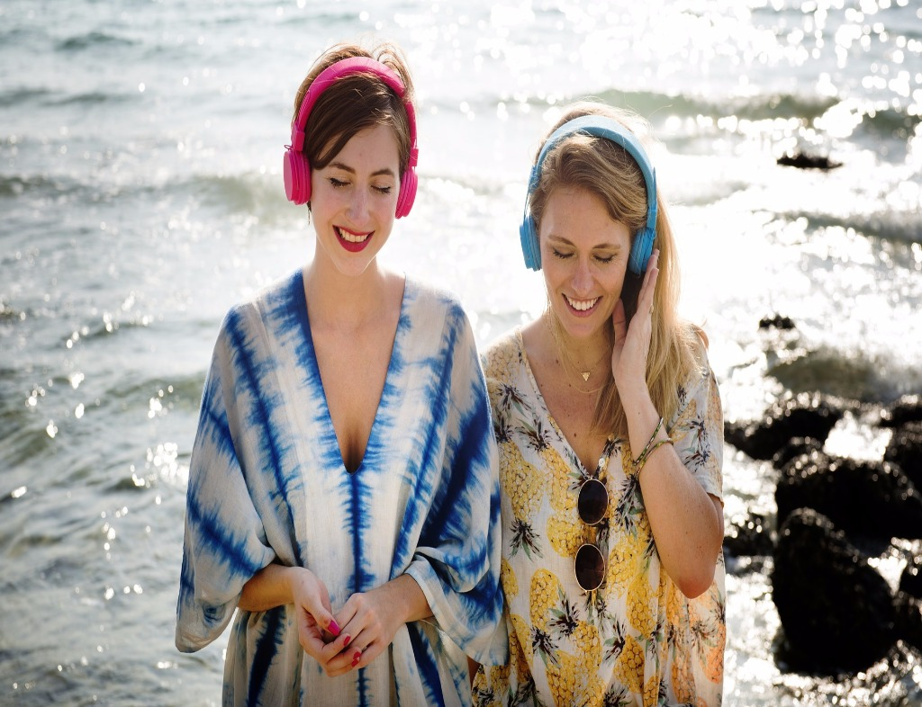 Two women standing with their backs turned to a shore with small waves. The woman on the left is wearing pink headphones and a blue and white top. Her hands are together in front of her. The woman on the right wears sky blue headphones and holds them up with her left hand. She is wearing a top that has prints of pineapples. Sunglasses are clasped to it.